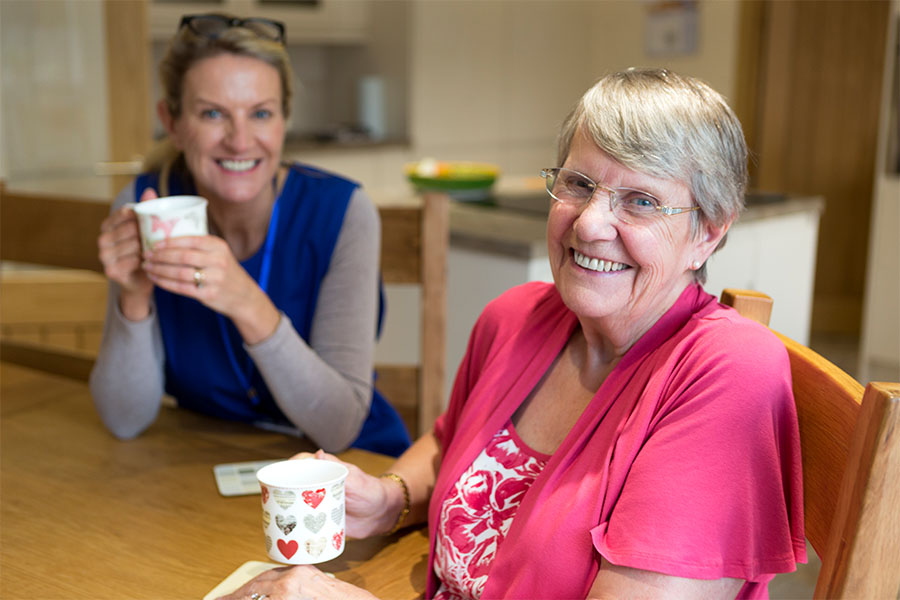 Two women sitting at a table enjoy coffee, one older woman and one younger caregiver.