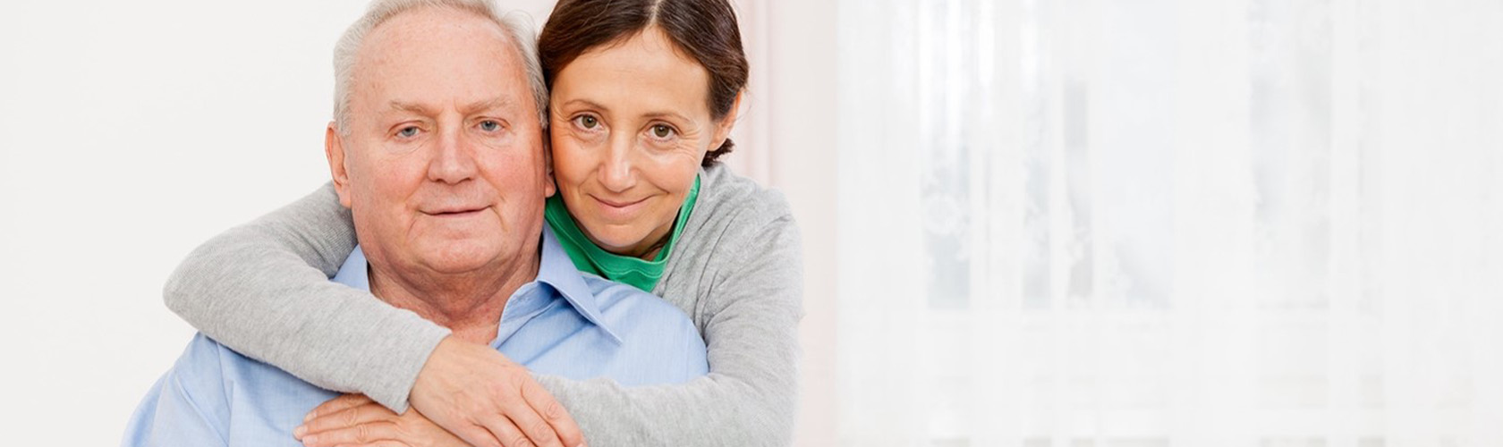 A woman with her arms around the shoulders of an older man.